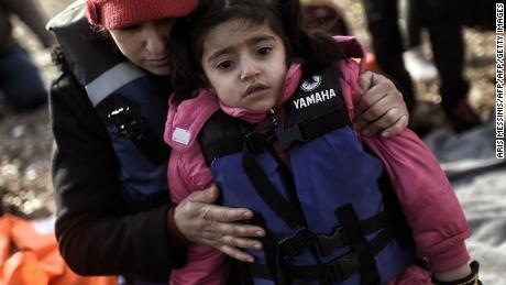 A woman hugs a young child as they arrive with other migrants on Lesbos in 2016.