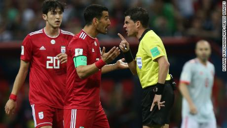 Uruguayan referee Andres Cunha speaks with Iran's midfielder Ehsan Haji Safi after the disallowed goal.
