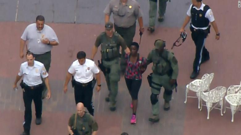 The protester who climbed onto the Statue of Liberty is led away by police on July 4, 2018.