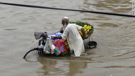 A street vendor in Lahore pushes a bike loaded with mangoes through the flooded streets on July 3, 2018.