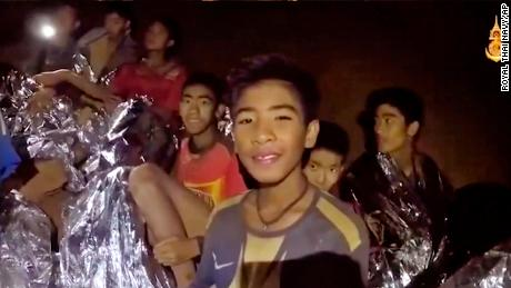 Some of the trapped boys smile as a Thai Navy SEAL medic offers assistance inside the cave on Tuesday.