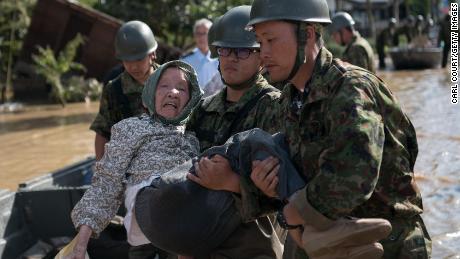 Soldiers carry an elderly woman away from flood water on July 8, 2018 in Kurashiki near Okayama, Japan.