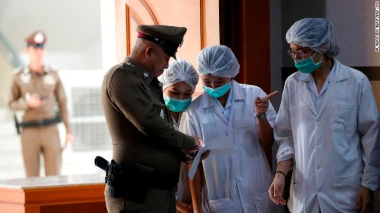Thai hospital staff and a police officer at Chiang Rai Prachanukroh Hospital on Tuesday.