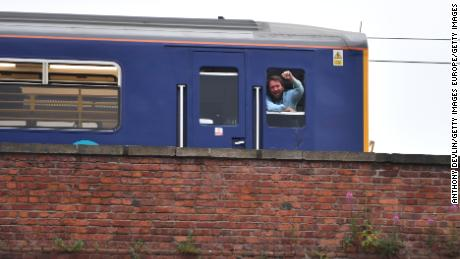 A train driver in Manchester, England, stops and watches a big screen event showing England vs. Croatia.