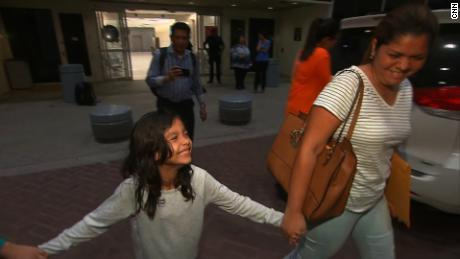 Alisson Madrid smiles as she grips the hand of her mother, Cindy, after their reunion early Friday in Houston.
