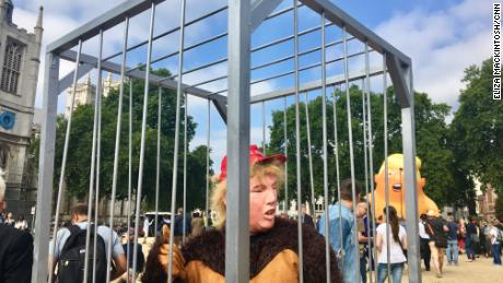 Gareth Steel, dressed in a Trump mask and gorilla costume, protests with an anti-Brexit group from inside a cage.