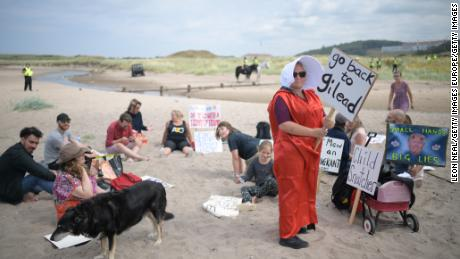 """A woman wears a costume in the style of the """"Handmaid's Tale"""" on a beach near Turnberry."""