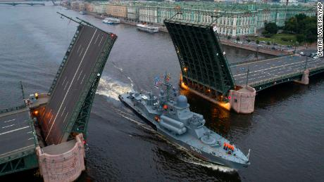 A Russian warship sails past the Dvortsovy drawbridge rising above the Neva River during rehearsals for the Navy Day parade in St. Petersburg.