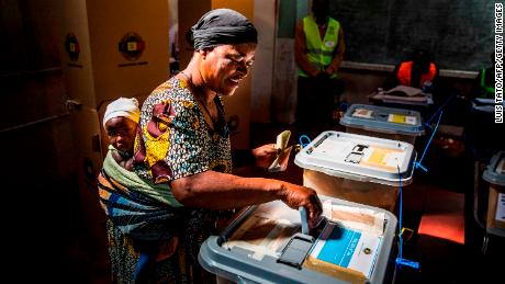 A woman carrying her baby casts her ballot in a polling station in the suburb of Mbare on Monday.