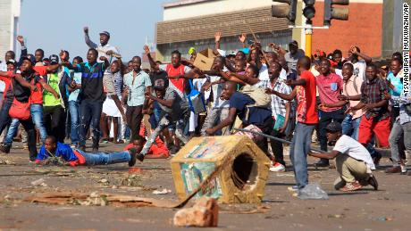 Opposition supporters react after police fire tear gas in Harare on Wednesday.