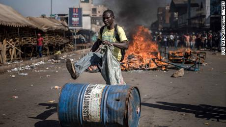 A supporter of the opposition pushes a barrel in front of a fire during a protest this week in Harare.