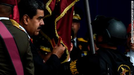 Venezuelan President Nicolas Maduro (L) attends a ceremony to celebrate the 81st anniversary of the National Guard in Caracas on August 4, 2018. - Maduro was unharmed after an exploding drone