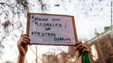 "An activist in favour of the legalization of abortion holds a sign reading ""Take out your Rosaries from our ovaries"" during a demonstration outside of Argentina's embassy in Santiago de Chile."