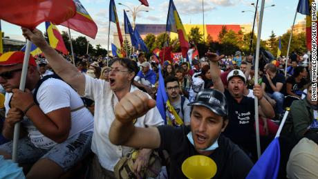 Protesters gather outside government offices in Bucharest on Saturday.
