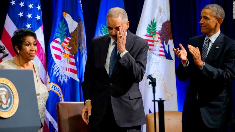 An emotional Attorney General Eric Holder, center, and President Barack Obama react after Franklin finished singing a song for Holder at an event celebrating the end of his tenure at the Department of Justice in 2015.