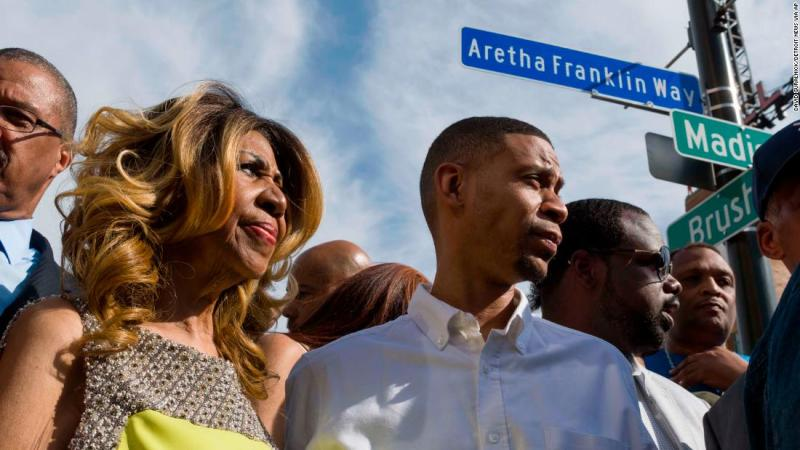 Franklin and her son Kecalf Cunningham stand under a newly unveiled street sign named in her honor outside Detroit's Music Hall in 2017.