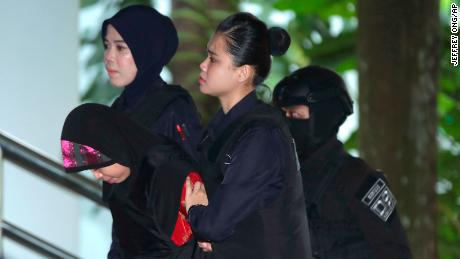 Siti Aisyah, left, is escorted by police as she arrives for Thursday's hearing at Shah Alam High Court.