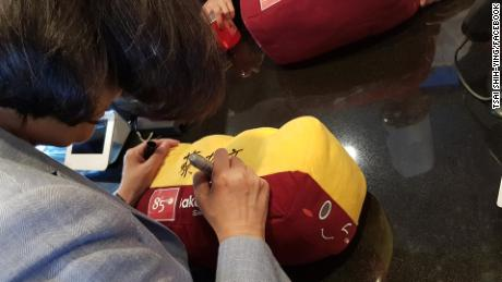Taiwan President Tsai Ing-wen signs a toy loaf of bread at an 85C bakery in Los Angeles on August 12, 2018.