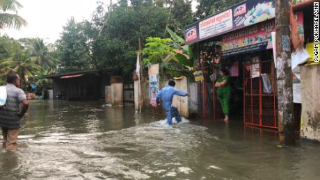 Residents of Venmoney in Kerala wait outside their homes and shops for relief.