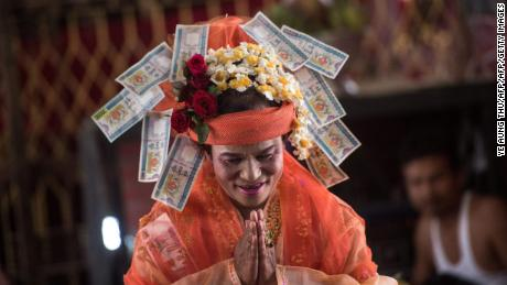 Mediums spin around in a frenzy of red and gold while glugging from a bottle of whiskey, part of an age old ritual to honour Myanmar's spirit guardian of drunkards and gamblers.