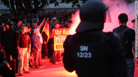 Riot police watch right-wing supporters the day after a man was stabbed to death in Chemnitz.