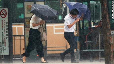 Pedestrians try to hold their umbrellas while struggling with strong winds in Yokohama, near Tokyo.
