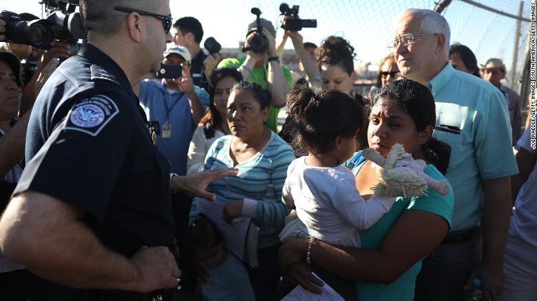 Migrant families seeking asylum encounter Border Patrol agents at the US-Mexico border in June 2018.