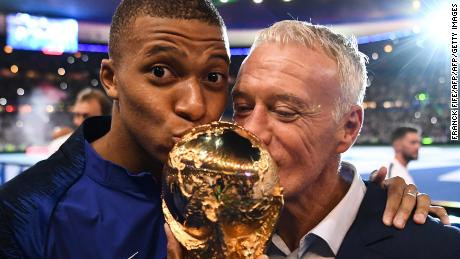 Mbappe and France coach Didier Deschamps kiss the World Cup as they celebrate during a ceremony in Paris after victory over the Netherlands.