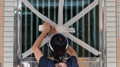 A resident tapes up her front entrance window in the fishing village of Tai O in Hong Kong on September 15, 2018.