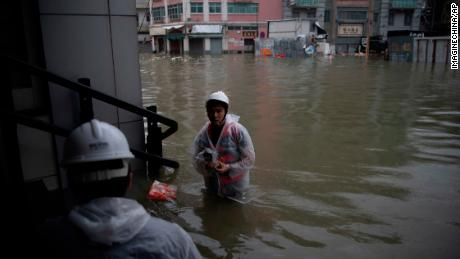Rescuers evacuate local residents from flooded areas in heavy rains caused by Typhoon Mangkhut in Macau.