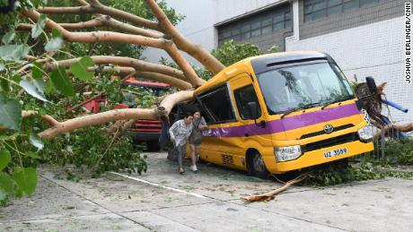 A school bus in Hong Kong's Heng Fa Chuen is left crushed by a tree during Typhoon Mangkhut.