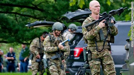 FBI tactical agents stand ready to assist as police search for a shooter Thursday.