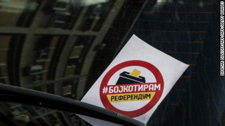 """A flyer reading """"I boycott"""" is seen on the windscreen of a car in Skopje."""