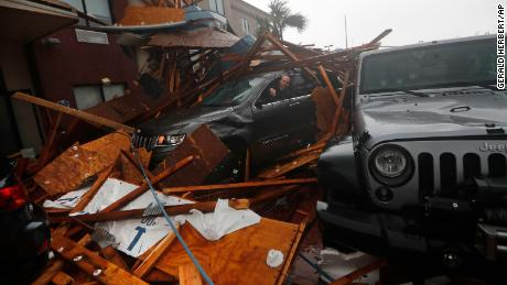 A storm chaser tries to get equipment from a vehicle after a hotel canopy fell in Panama City Beach.