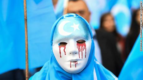 A person wearing a white mask with tears of blood takes part in a protest march of ethnic Uyghurs asking for the European Union to call upon China to respect human rights Xinjiang in April 2018.