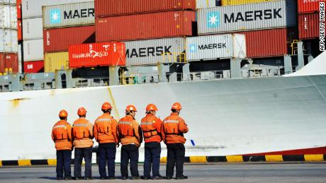 This photo taken on April 8, 2018 shows workers stand in line next to a container ship at a port in Qingdao in China's eastern Shandong province.