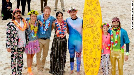 Britain's Prince Harry and Meghan, Duchess of Sussex pose for a photo with local surfing community group at Bondi Beach in Sydney, on October 19.