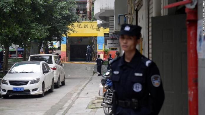 Police officers are seen outside the gate of a kindergarten where a woman armed with a kitchen knife attacked children in Chongqing on October 26.