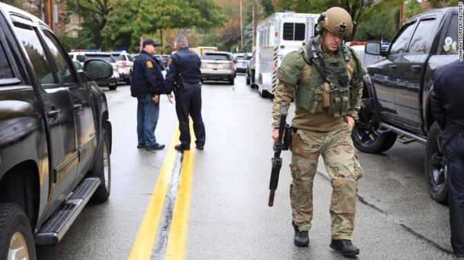 A SWAT police officer and other first responders respond after a gunman opened fire at the synagogue.