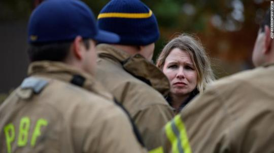 An unidentified woman asks for a status update from Pittsburgh City firefighters a block away from the site of the synagogue shooting.