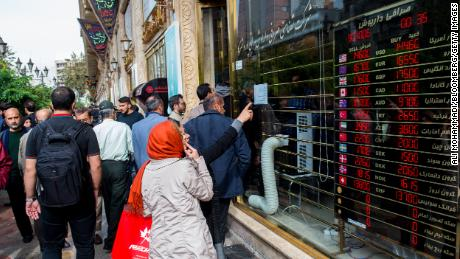 Pedestrians look at currency exchange rates in the window of a store in Tehran on Saturday.
