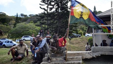 An activist holds the pro-independant flag during a meeting of the Kanak and Socialist National Liberation Front (FLNKS) campaign for a 'yes' to New Caledonia's independence from France in Noumea.
