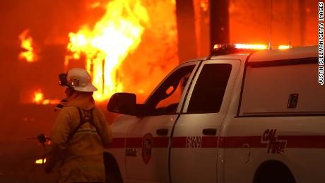 A Cal Fire firefighter monitors a burning home as the Camp Fire moves through the area.