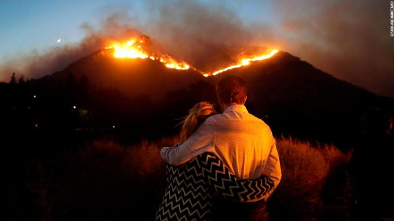 Roger Bloxberg and his wife, Anne, hug as they watch a wildfire on a hilltop Friday, near their home in the West Hills area of Los Angeles.