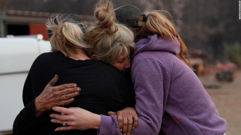 Cathy Fallon, who stayed behind to tend to her horses during the Camp Fire in Paradise, embraces Shawna De Long, left, and April Smith, right, who brought supplies for the horses.