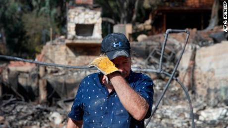 Roger Kelton, 67, wipes his tears while searching through the remains of his mother-in-law's home.
