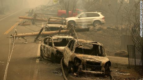 Power lines rest on cars that were burned by the Camp Fire on November 10, 2018 in Paradise, California.