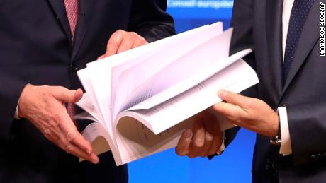 EU chief Brexit negotiator Michel Barnier, left, and European Council President Donald Tusk flip through the draft withdrawal agreement.