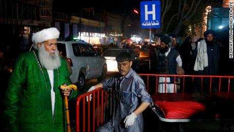 Afghan religious scholars wait outside the emergency hospital after a suicide bomber targeted a religious gathering at a wedding hall in Kabul.