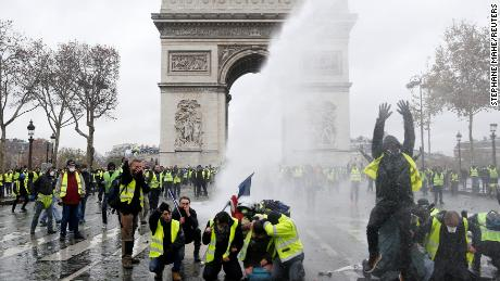 Protesters wearing yellow vests, a symbol of a French drivers' protest against higher diesel taxes, stand up in front of a police water canon at the Place de l'Etoile near the Arc de Triomphe in Paris, France, December 1, 2018. REUTERS/Stephane Mahe